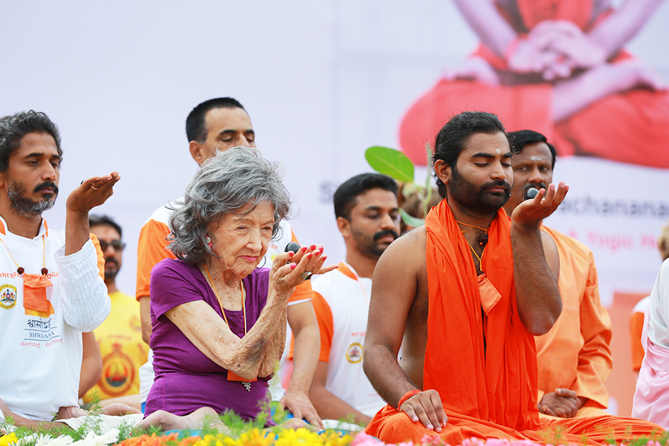 98-year-old yoga master Tao Porchon-Lynch and Shwaasa Guru meditating on stage at International Day of Yoga at Kanteerava Outdoor Stadium in Bangalore, India - June 21, 2017